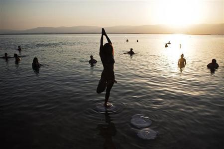 A woman practices yoga during a mass floating event in the Dead Sea September 14, 2012. REUTERS/Nir Elias/Files