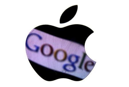 A Google trademark is reflected in Apple logo in this photo illustration taken in Berlin, August 31, 2012. REUTERS/Pawel Kopczynski