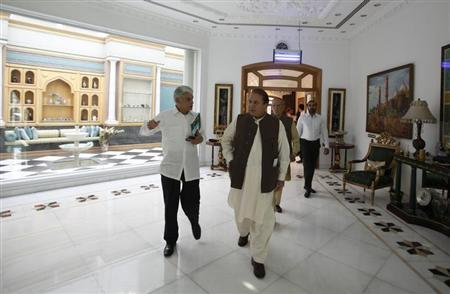 Nawaz Sharif (R) leader of political party Pakistan Muslim League - Nawaz (PML-N) walks with his personal secretary Asif Kirmani at his house in Lahore May 4, 2013. REUTERS/Mohsin Raza
