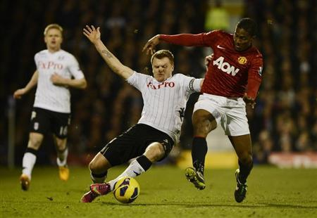 Fulham's John Arne Riise (C) is challenged by Manchester United's Antonio Valencia during their English Premier League soccer match at Craven Cottage stadium in London February 2, 2013. REUTERS/Dylan Martinez