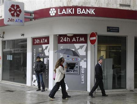 Cypriots walk pass a Cypriot bank on the island's capital Nicosia, April 18, 2013. REUTERS/Andreas Manolis