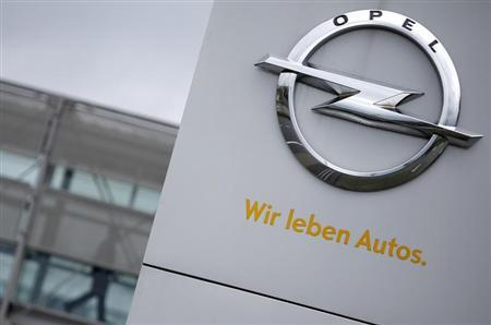 A sign depicting the Opel logo is pictured in front of the Opel Adam AG headquarters as a person passes by in Ruesselheim April 10, 2013. The sentence reads: ''We live cars''. REUTERS/Lisi Niesner