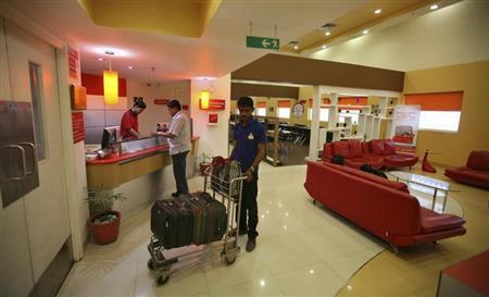 An attendant holds a trolley loaded with the luggage of a guest at the reception area of the Tata Group's Indian Hotels Co. Ginger chain in Ahmedabad May 5, 2012. REUTERS/Amit Dave/Files