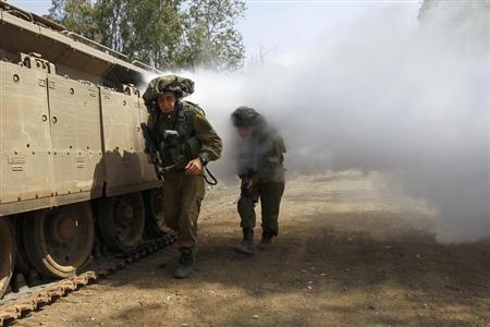 Soldados israelíes a pie a través del humo que se entrenan en la guerra urbana cerca de la línea de alto el fuego entre Israel y Siria, por Israel Altos del Golán ocupados 06 de mayo 2013.  REUTERS / Baz Ratner