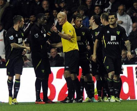 Norwich City's Sebastien Bassong (2nd L) speaks to the referee Howard Webb after their fourth goal during their English Premier League soccer match at the Liberty Stadium in Swansea, South Wales December 8, 2012. REUTERS/Rebecca Naden