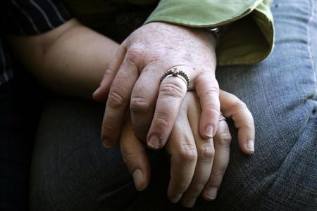 A gay couple hold hands as they look at wedding photo at their home in San Francisco, California June 11, 2008. REUTERS/Erin Siegal
