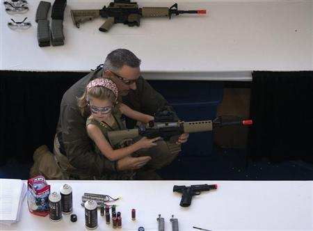 A man shows a girl how to hold an airsoft gun during the NRA Youth Day at the National Rifle Association's annual meeting in Houston, Texas on May 5, 2013. REUTERS/Adrees Latif