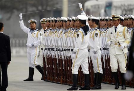 Members of the People's Liberation Army's navy guard of honour prepare to use a string to ensure that soldiers stand in a straight line before an official welcome ceremony outside the Great Hall of the People, in Beijing April 15, 2013. REUTERS/Jason Lee