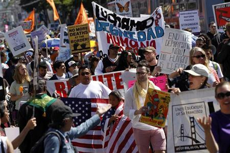 Demonstrators carry signs during an immigration rally on May Day in the Mission District in San Francisco, California May 1, 2013. REUTERS/Robert Galbraith