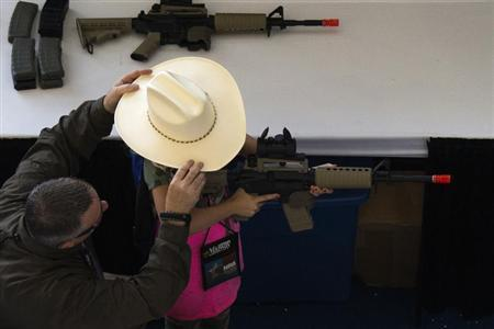 A man adjusts a girl's hat before she takes aim with an airsoft gun during the NRA Youth Day at the National Rifle Association's annual meeting in Houston, Texas on May 5, 2013. REUTERS/Adrees Latif