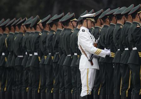 A member of the People's Liberation Army's navy guard of honour adjusts military uniforms before an official welcome ceremony outside the Great Hall of the People, in Beijing April 15, 2013. REUTERS/Jason Lee