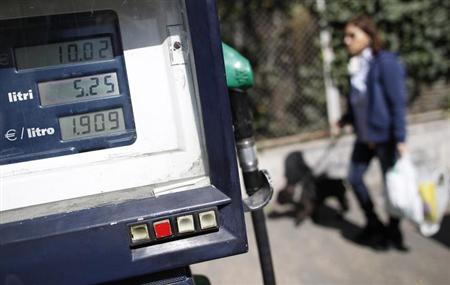 A woman walks past a meter at a petrol station in downtown Rome March 13, 2012. REUTERS/Tony Gentile