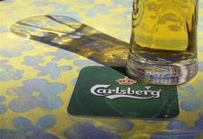Бокал пива стоит на подставке с логотипом Carlsberg в баре в Риге, 6 мая 2013 года. Операционная прибыль и выручка датского пивовара Carlsberg в первом квартале превзошли прогнозы благодаря сильным продажами пива в Азии, компенсировавшим спад в Западной Европе и России. REUTERS/Ints Kalnins