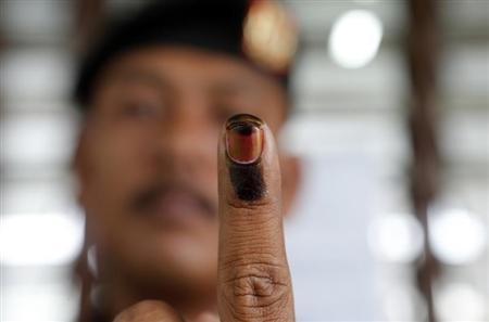 A Malaysian voter shows his finger marked with ink after casting his ballot during the early voting for the general elections in Kuala Lumpur April 30, 2013. REUTERS/Bazuki Muhammad