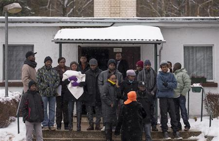 Asylum seekers stand outside an accommodation at a refugee holding centre in the town of Bad Belzig some 135 km (84 miles) south-west of Berlin, December 12, 2012. REUTERS/Thomas Peter