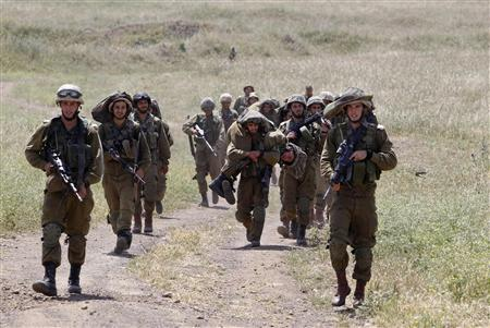 Israeli soldiers walk together during training close to the ceasefire line between Israel and Syria on the Israeli occupied Golan Heights May 7, 2013. REUTERS/Baz Ratner