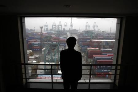An employee views the Port of Shanghai from an office window, January 19, 2011. REUTERS/Carlos Barria