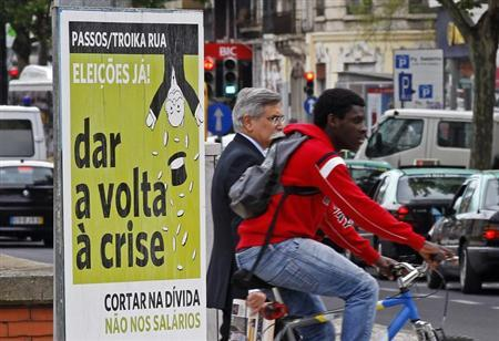 People pass by a political poster reading, ''Passos/Toika out. Elections now. Turn the crisis around. Cut the debt and not the salaries'', on a street in Lisbon May 7, 2013. REUTERS/Jose Manuel Ribeiro