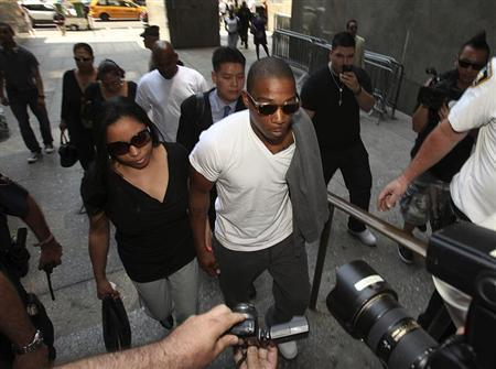Ja Rule (R), accompanied by his wife Aisha Atkins (L), arrives at the Manhattan Supreme Court, to begin a two-year prison sentence in New York June 8, 2011. REUTERS/Andrew Kelly