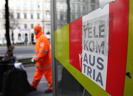 A trash collector walks by a Telekom Austria phone box in Vienna February 8, 2013. REUTERS/Heinz-Peter Bader