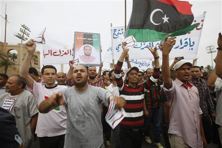Protesters wave a Libyan flag as they demonstrate in Martyrs' Square demanding Gaddafi-era officials to be banned from taking up political posts, in Tripoli May 5, 2013. REUTERS/Ismail Zitouny