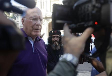Democratic Senator Patrick Leahy of Vermont speaks to reporters as a street entertainer impersonating Cuban Revolution leader Che Guevara stands beside him in Havana February 20, 2013. REUTERS/Desmond Boylan