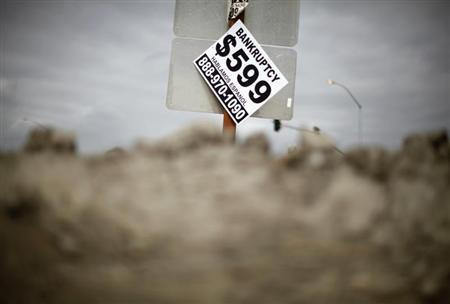 A sign advertising bankruptcy filing is seen hanging off a road sign in San Bernardino, California September 11, 2012. REUTERS/Lucy Nicholson