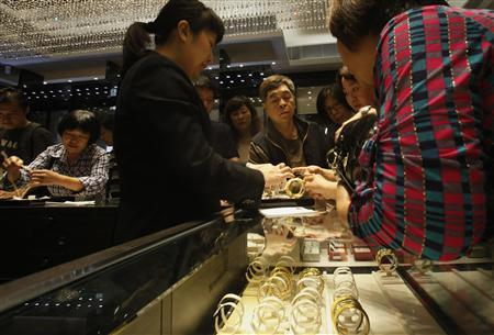 A sales attendant shows a gold bracelet to customers leaning over a half-empty display case at a jewellery store in Hong Kong April 26, 2013. REUTERS/Bobby Yip