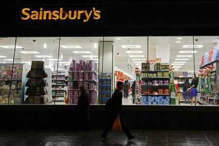 People walk past a Sainsbury's store in south London November 11, 2009. British grocer J Sainsbury posted a forecast-beating 19 percent rise in first-half profit and said it saw signs of a pick-up in spending, though industry growth would be curbed by lower food price inflation. REUTERS/Stefan Wermuth