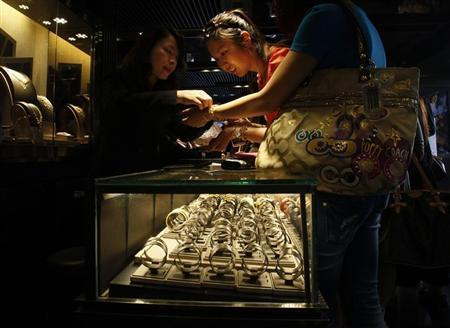 A mainland Chinese visitor tries a 24K gold bracelet as near-empty shelves are seen inside a jewellery store at Hong Kong's Tsim Sha Tsui shopping district April 24, 2013. REUTERS/Bobby Yip/Files