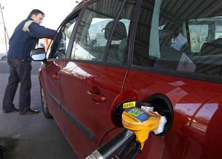 A driver pumps petrol into his car at a petrol station in Brussels March 8, 2011. REUTERS/Yves Herman/Files