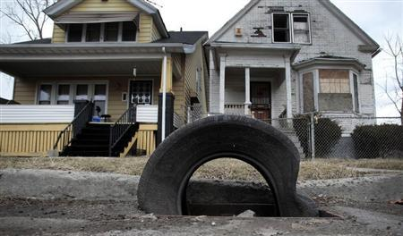 A tire sits on a storm drain as a replacement for a cast iron grate, stolen for scrap, in front of a well-kept home and vacant home in a neighborhood where many of the grates are missing on the east side of Detroit, Michigan March 19, 2013. REUTERS/ Rebecca Cook