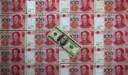 Стодолларовая банкнота лежит на пачках китайских юаней, фотография сделана в Пекине 7 мая 2013 года. Центробанк Китая в среду дал понять, что готовится изменить свою монетарную стратегию, чтобы избежать притока спекулятивного капитала, поскольку Пекин не в состоянии контролировать волну денег, нахлынувшую с зарубежных рынков. REUTERS/Petar Kujundzic