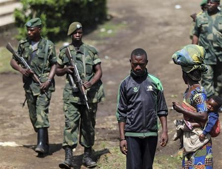 A man walks as Congolese army (FARDC) soldiers patrol in Minova, some 45 km (28 miles) west of Goma November 26, 2012. REUTERS/Goran Tomasevic