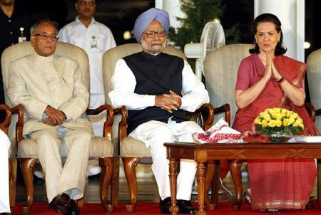 Chief of ruling Congress party Sonia Gandhi (R) gestures as Prime Minister Manmohan Singh (C) and Finance Minister Pranab Mukherjee watch during the release of a book titled 'Report To The People 2010-11' by the government of United Progressive Alliance (UPA) in New Delhi May 22, 2011. REUTERS/B Mathur/Files