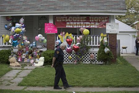 A Cleveland police officer is present outside the home of Amanda Berry's sister in Cleveland, Ohio, May 8, 2013. REUTERS-John Gress