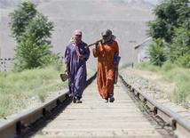 Женщины шагают по железной дороге у селения Сангтуда на юге Таджикистана 28 мая 2008 года. Президенты Туркмении и Казахстана в субботу дадут старт строившейся пять с половиной лет железной дороге, призванной сократить богатым углеводородами и зерном странам Каспия путь к рынкам Персидского залива, снижая зависимость от российского и узбекского транзита. REUTERS/Shamil Zhumatov