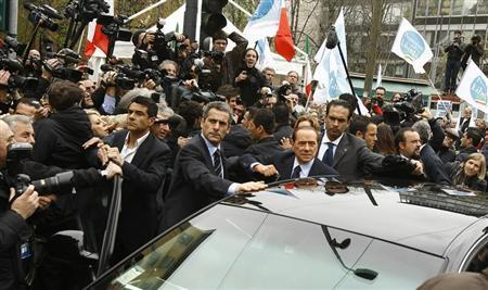 Italy's Prime Minister Silvio Berlusconi (C) leaves the Justice Palace in Milan March 28, 2011. REUTERS/Alessandro Garofalo