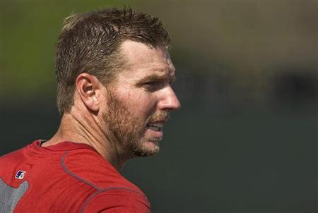 Philadelphia Phillies pitcher Roy Halladay takes a breather during a workout before a MLB spring training baseball game with the New York Yankees in Clearwater, Florida, March 19, 2013. REUTERS/Steve Nesius
