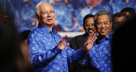Malaysia's Prime Minister Najib Razak (L) and his deputy Muhyiddin Yassin share a light moment after winning the elections at his party headquarters in Kuala Lumpur early May 6, 2013. REUTERS/Bazuki Muhammad