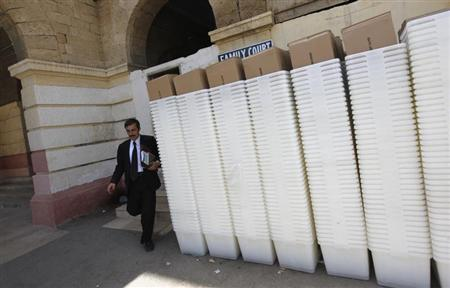 A man walks past rows of election ballot boxes, before they are transported to polling offices, in the premises of the district city court in Karachi May 8, 2013. REUTERS/Akhtar Soomro