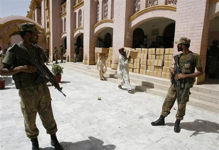 Soldiers stand guard outside a district court as election commission workers carry election materials in Hyderabad May 8, 2013. REUTERS/Akram Shahid