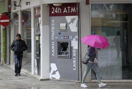 Cypriots walk pass a Cypriot bank on the island's capital Nicosia, April 18, 2013.REUTERS/Andreas Manolis