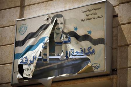 A torn picture of Syria's President Bashar al-Assad is seen on a government building in Raqqa province, east Syria May 8, 2013. REUTERS/Hamid Khatib
