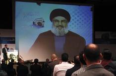 حسن نصر الله يتحدث لأنصاره عبر شاشة عملاقة أثناء احتفال في بيروت يوم الخميس. تصوير: شريف كريم - رويترز