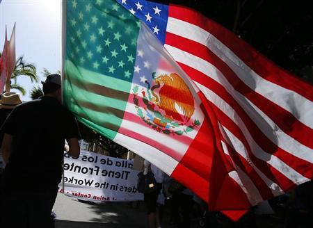 A youth carries national flags of the U.S. and Mexico through the streets of San Diego, during a May Day demonstration and march in California May 1, 2013. REUTERS/Mike Blake