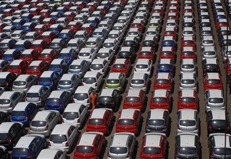 An employee walks between parked Hyundai cars ready for shipment at a port in Chennai February 22, 2010. REUTERS/Babu