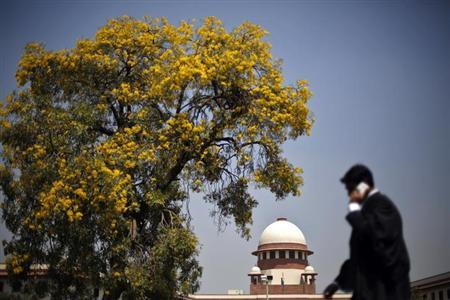 A lawyer speaks on his mobile phone as he walks past Supreme Court in New Delhi April 1, 2013. REUTERS/Adnan Abidi/Files