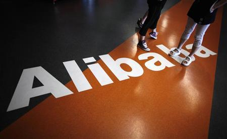 Employees stand on a logo of Alibaba (China) Technology Co. Ltd during a media tour organised by government officials at its headquarters on the outskirts of Hangzhou, Zhejiang province June 20, 2012. REUTERS/Carlos Barria