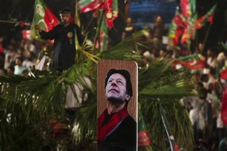 A supporter of Imran Khan, a Pakistani cricketer-turned-politician and chairman of the Pakistan Tehreek-e-Insaf (PTI) political party, holds up a cricket bat with an image of Khan during a rally on the last day of the election campaign in Islamabad May 9, 2013. REUTERS/Mian Khursheed